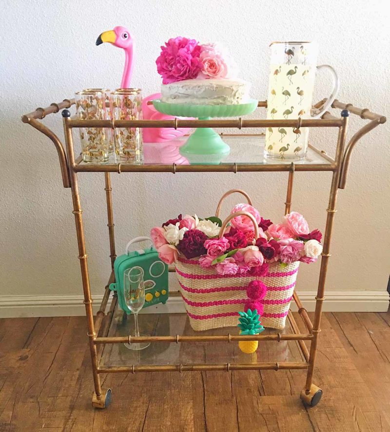 Lifestyle blogger Candace Rose adorned her gold faux bamboo bar cart with flamingo decor must haves, garden roses, and a straw tote for summer! Candieanderson.com blog faux bamboo bar carts