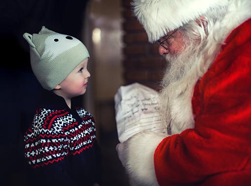 Toddler with Santa Claus talking about holiday wish lists. Learn how to set a holiday budget for your entire family during Candace Rose Anderson's recent interview with Country Financial, financial expert Tim Harris.